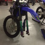 Motocross bike on stand with wheels taken off