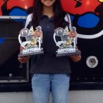 Young woman holding up 2 motocross trophies