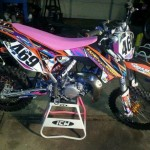 Custom painted motocross bike on stand in shop
