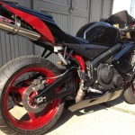 Custom black and red street bike with large exhaust under seat