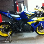 Large blue and yellow street bike in paint shop