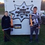 Young boys holding up motocross trophies with Mad Brothers Cycles trailer in background